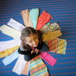Five year old, C, sits center circle in the order of fabrics arranged solely by her.