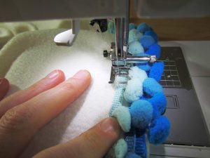 Fleece doesn't fray when cut. Because of this, you can decide to add reinforced stitching on the longer (non-pom pom) side or not.