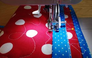 Then I used a basting stitch & sewed the bottom of the tube to the back of the quilt.