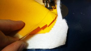 Cut snips into the fabric as you go around the corners.